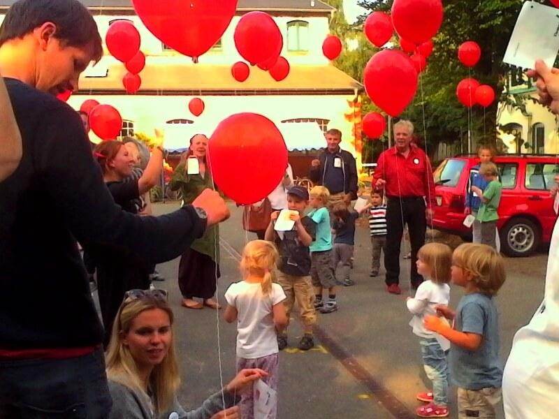 Kinder lassen gemeinsam mit ihren Eltern rote Luftballons in den Himmel steigen.