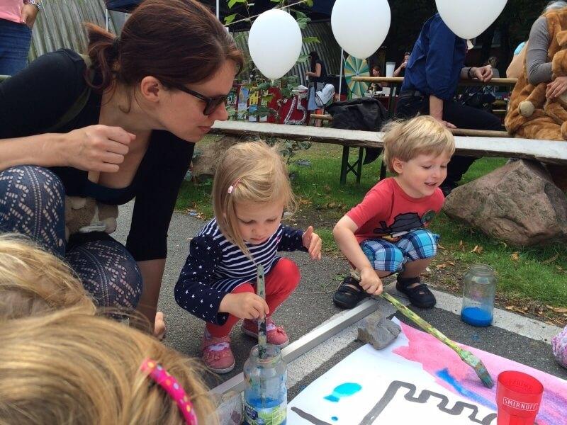 Kinder bemalen mit bunten Farben eine Leinwand