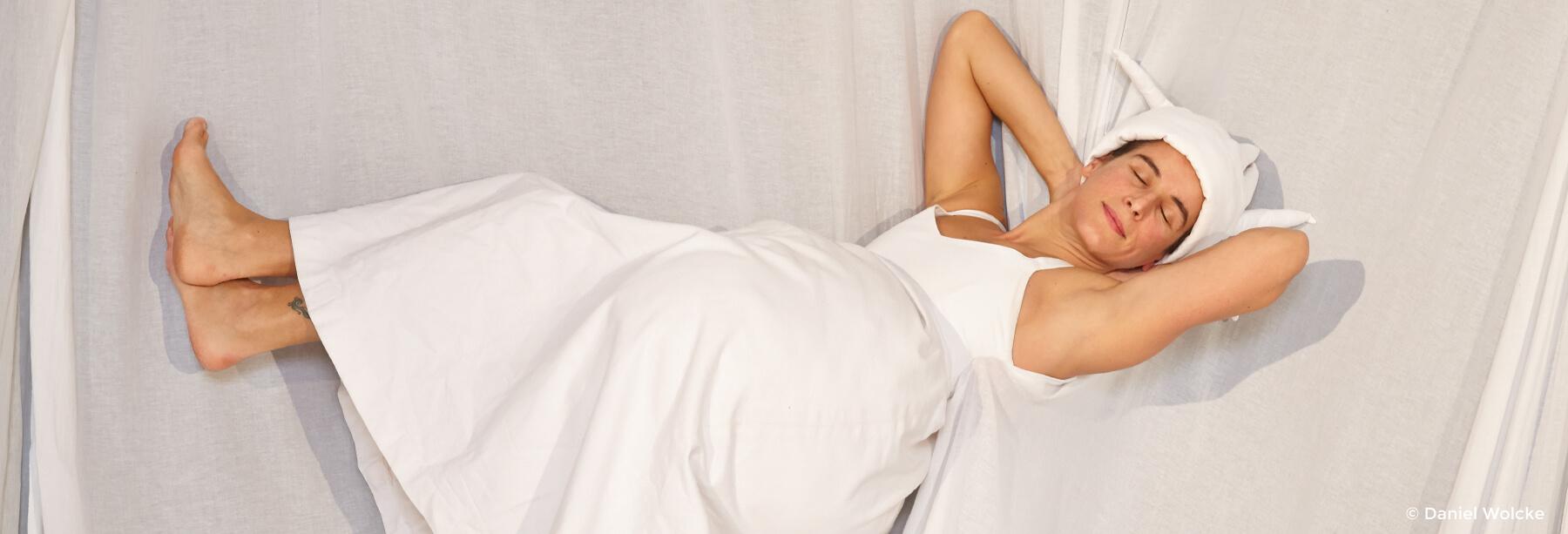 Die Königin der Farben: Marcella Ruscigno liegt auf einem weißen Bett.