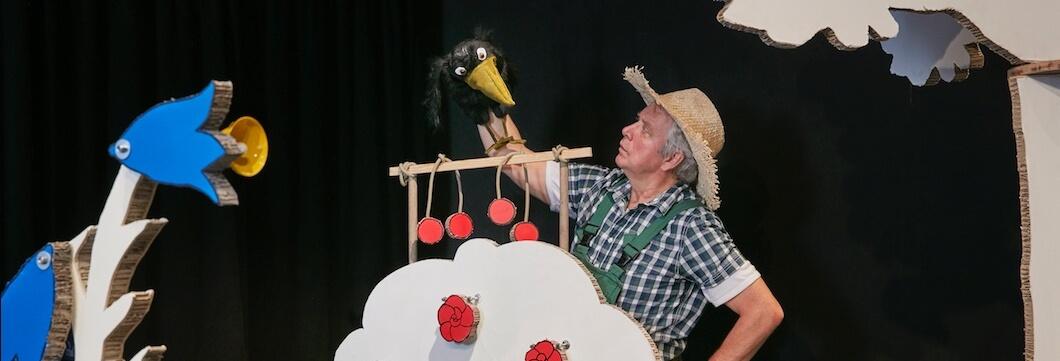 Peter Markhoff und der Rabe in der Kulisse des Theaterstücks Obstgärtchen