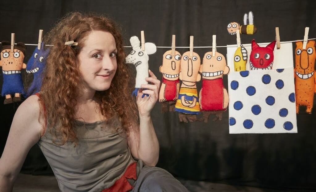 Iris Faber vor der Wäscheleine, an der viele unterschiedliche Charaktere hängen.