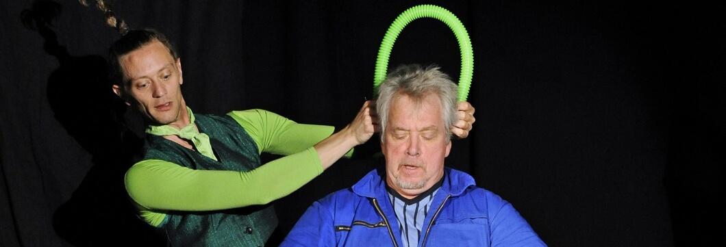 Grün angezogener Mann fasst blau angezogenem Mann an den Kopf.