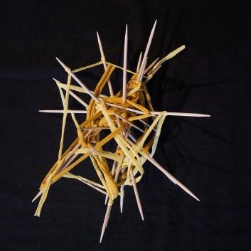 Selbstgebastelter runder Stern aus Zahnstochern und gelbem Faden