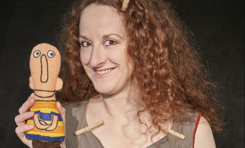 Iris Faber hält einen Charakter aus dem Theaterstück Eins Zwei Drei Tier in die Kamera.