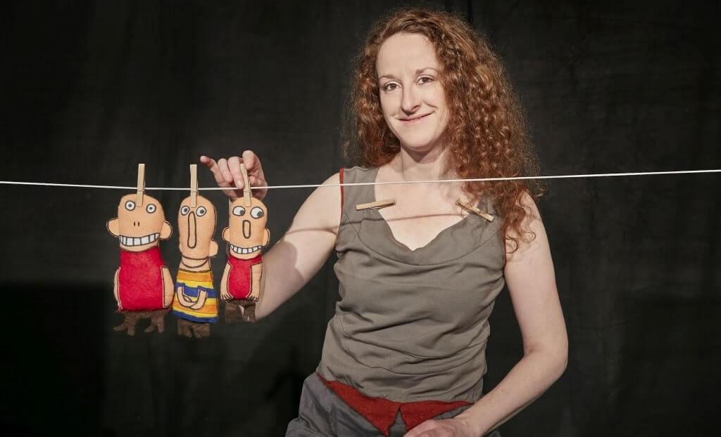 Iris Faber mit drei Figuren, die an einer Wäscheleine hängen.